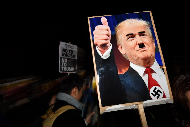 A demonstrator holds a placard showing a picture of US President-elect Donald Trump modified to add a swastika and an Adolf Hitler-style moustache during a protest outside the US Embassy in London November 9, 2016 against Trump after he was declared the winner of the US presidential election. (AFP PHOTO / BEN STANSALL)