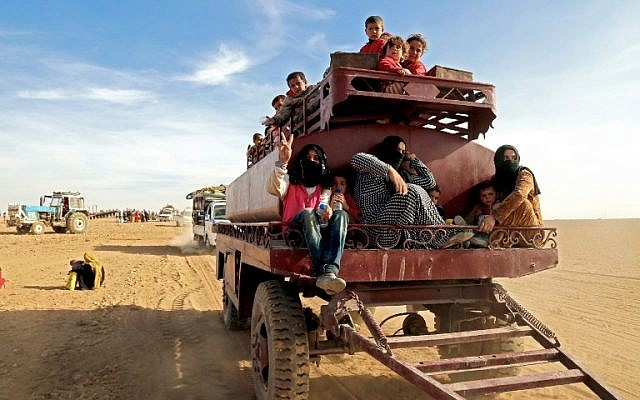 A child raises a victory sign while riding a towed storage tank carrying other Syrians fleeing areas controlled by jihadists of the Islamic State (IS) group, as they come to safety in areas held by by Kurdish-Arab Syrian Democratic Forces (SDF) alliance, near the village of Mazraat Khaledon, November 9, 2016, (AFP/DELIL SOULEIMAN)