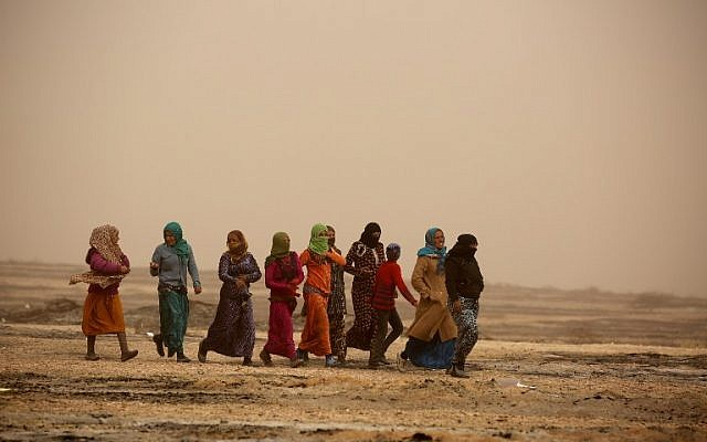 Syrian women walk during a sandstorm at a temporary refugee camp in the village of Ain Issa, housing people who fled Islamic State group's Syrian stronghold Raqqa, November 10, 2016. (AFP/DELIL SOULEIMAN)