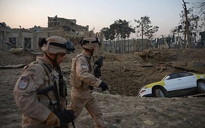 Croatian soldiers from the NATO coalition walk past a crater from a bomb blast as they inspect the site of an attack targeting the German consulate in Mazar-i-Sharif, Afghanistan on November 11, 2016. (AFP/Farshad Usyan)