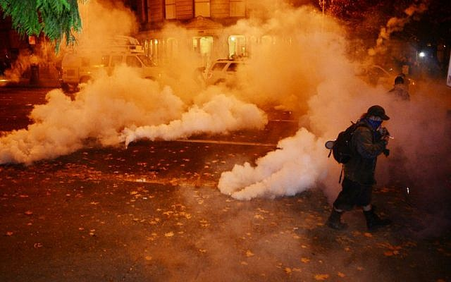 A protester walks through smoke and tear gas at City Hall in downtown Portland, as hundreds gather to voice their opinion following the US elections on November 11, 2016. ( AFP PHOTO / ALD Photography / Ankur Dholakia)