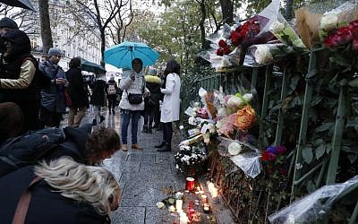 People gather around flowers and candles laid next to the Bataclan concert hall in Paris on November 12, 2016, a few hours before the reopening concert by British musician Sting to mark the first anniversary of the November 13 Paris attacks.(AFP PHOTO / FRANCOIS GUILLOT)