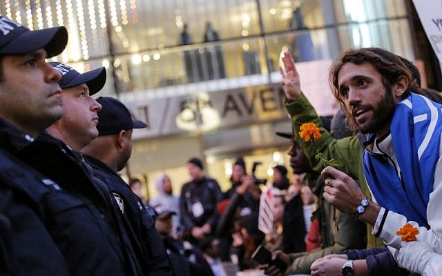 A demonstrator speaks with NYPD officers as he protests against US President-elect Donald Trump in front of Trump Tower on November 12, 2016 in New York.(AFP PHOTO / KENA BETANCUR)