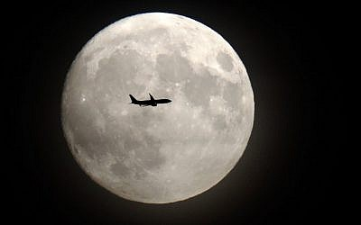 A commerical jet flies in front of the moon on its approach to Heathrow airport in west London on November 13, 2016. (AFP/Adrian DENNIS)