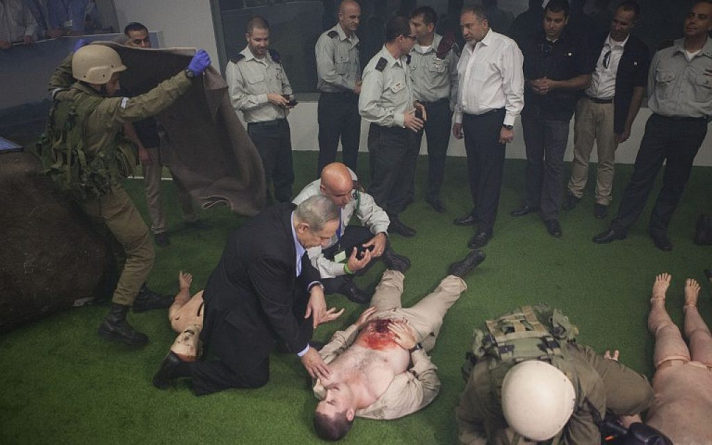Prime Minister Benjamin Netanyahu (L) and Israeli defense Minister Avigdor Lieberman (4-R), are seen next to soldiers doing a rescue simulation during a visit at the new training military base next to the southern city of Beer Sheva on November 15, 2016. (AFP PHOTO / POOL AND AFP PHOTO / Dan Balilty)