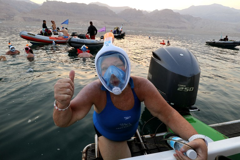 A woman taking part in a 18-kilometre swim from Jordan to Israel across the Dead Sea, organised by the EcoPeace charity aimed at raising awareness for the iconic water body which has been receding by roughly a metre each year, gives the thumbs up upon the departure from Jordan on November 15, 2016. (AFP PHOTO / Gali TIBBON)