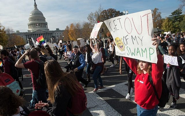 High school students march past the US Capitol in Washington, DC, on November 15, 2016 as they protest the election of US President-elect Donald Trump. (AFP/NICHOLAS KAMM)