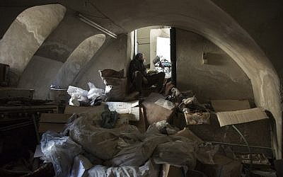 A member of the Syrian civil defense, known as the White Helmets, takes shelter in the basement of an old building during shelling in Aleppo's rebel-held neighborhood of Bab al-Nayrab on November 19, 2016. (AFP/Karam Al-Masri)