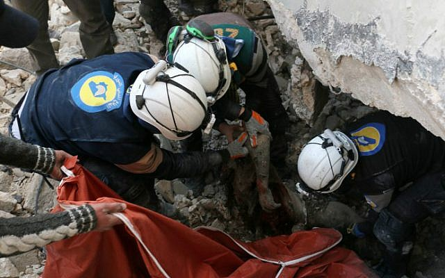 Syrian civil defense volunteers, known as the White Helmets, pull a body from the rubble of a destroyed building on November 19, 2016 following a reported air strike on Aleppo's rebel-held neighborhood of Bab al-Nayrab. (Ameer Alhalbi/AFP)