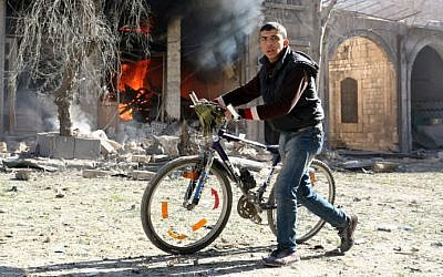 A Syrian youth pushes his bicycle past a burning house on November 19, 2016 following a reported air strike on Aleppo's rebel-held neighborhood of Bab al-Nayrab. (Ameer Alhalbi/AFP)