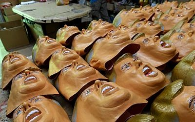 This picture taken on November 22, 2016 shows employees producing rubber masks of US President-elect Donald Trump at the Ogawa Studios mask factory in Saitama, north of Tokyo. (AFP PHOTO / TOSHIFUMI KITAMURA)
