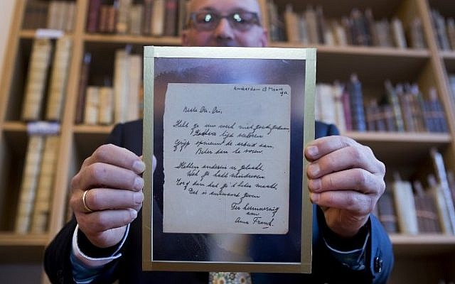 A man shows a handwritten poem by Anne Frank, written shortly before she went into hiding from the Nazis, at the auction Bubb Kuyper in Haarlem on November 22, 2016. (AFP PHOTO / ANP / Koen Suyk / Netherlands)