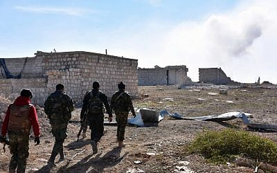 Syrian pro-government forces walk past damaged houses as they approach the Baeedin district in eastern Aleppo, near Masaken Hanano,  November 23, 2016. (GEORGE OURFALIAN / AFP)