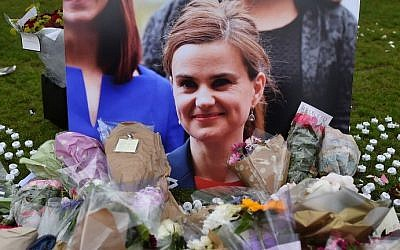 This photo taken on June 18, 2016 shows flowers and tributes laid in remembrance against a photograph of slain Labour MP Jo Cox in Parliament Square, central London, June 18, 2016. (AFP Photo/Ben Stansall)