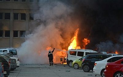 A fireman tries to extinguish burning cars cars after an explosion on November 24, 2016 in Adana, Turkey, in which two people were killed and 16 wounded. (AFP PHOTO/IHLAS NEWS AGENCY)