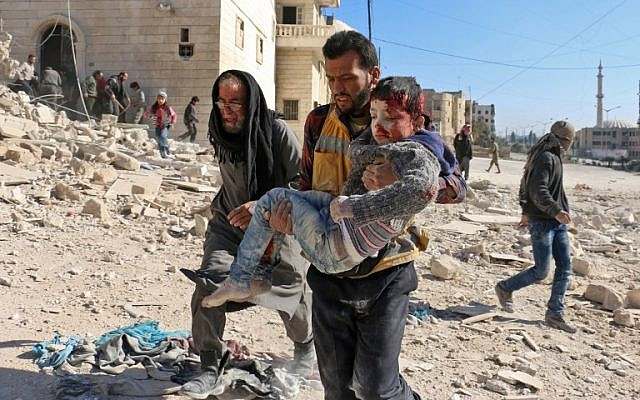 A Syrian civil defence volunteer, known as the White Helmets, carries a boy rescued from the rubble following a reported barrel bomb attack on the northern Syrian city of Aleppo on November 24, 2016. (/ AFP PHOTO / AMEER ALHALBI)