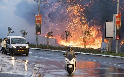 Israelis drive past a fire raging through the northern Israeli port city of Haifa on November 24, 2016. (Jack Guez/AFP)