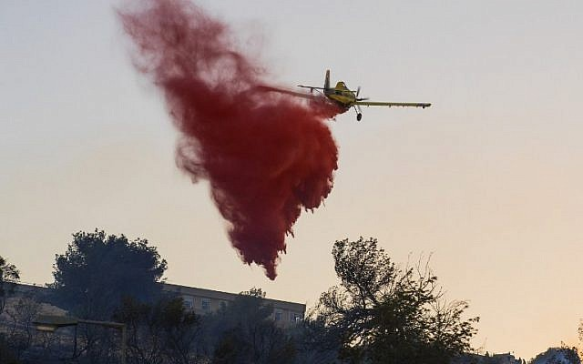 An Israeli firefighter plane helps extinguish a fire in the northern port city of Haifa, November 24, 2016. (AFP/JACK GUEZ)