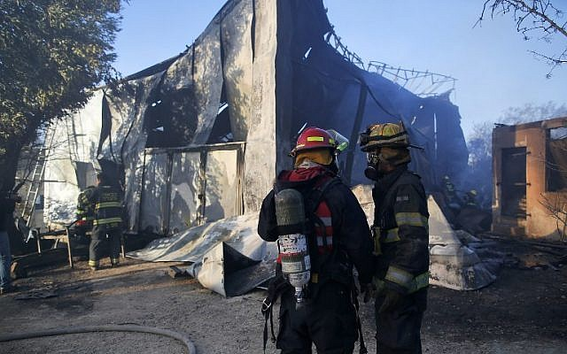 Israeli firefighters inspect the damage to the community of Beit Meir in the Jerusalem hills , on November 25, 2016. (AFP/Ahmad Gharabli)