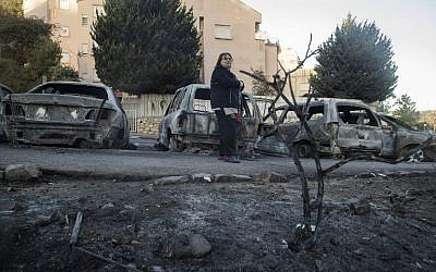 A woman stands amid the damage and burned vehicles in the northern Israeli city of Haifa following a wildfire, on November 25, 2016. (AFP/Jack Guez)