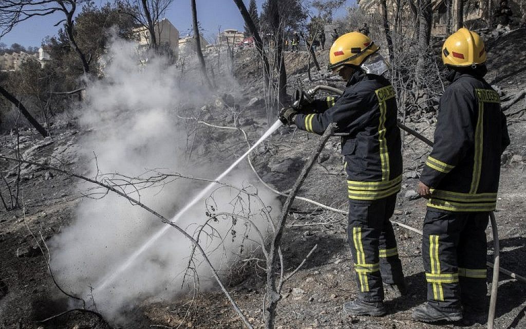 Israeli firefighters extinguish a fire in the northern Israeli city of Haifa following a wildfire, on November 25, 2016. (AFP/ JACK GUEZ)