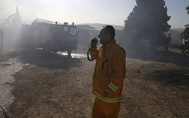 An Israeli firefighter uses a walkie-talkie to speak to his colleagues as they extinguish fire in Beit Meir, a village in the hills to the west of Jerusalem, on November 25, 2016. (AFP PHOTO / AHMAD GHARABLI)