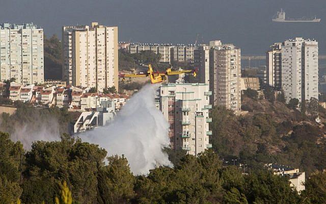 A firefighting plane helps extinguish a blaze in Haifa following a massive wildfire in the northern city, on November 25, 2016. (AFP PHOTO/MENAHEM KAHANA)