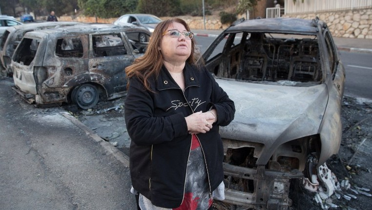 A woman walks past burned cars in the northern Israeli city of Haifa following a wildfire, on November 25, 2016. (AFP PHOTO / MENAHEM KAHANA)