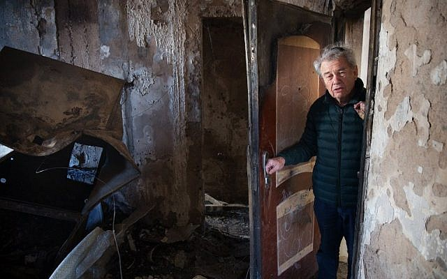 Eitan Shariel inspects the damage inside his house in the northern city of Haifa following a wildfire, on November 25, 2016. ( AFP PHOTO / MENAHEM KAHANA)