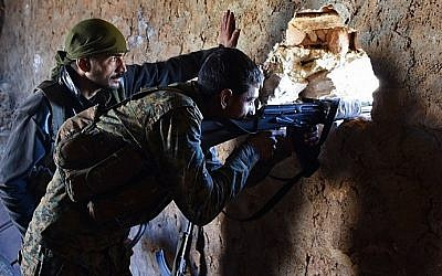 A fighter from the Syrian pro-government forces mans a riffle inside a damaged house in the recently recaptured village of Joubah during an offensive towards the area of Al-Bab in Aleppo province, on November 25, 2016. (AFP/George Ourfalian)