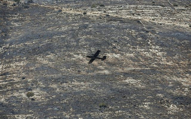 The shadow of a Turkish firefighter jet is seen as it flies over the village of Nataf close to Jerusalem, to help extinguish the ongoing fire in the area, on November 26, 2016. (AFP PHOTO/AHMAD GHARABLI)