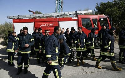 Palestinian firefighters arrive in the Jerusalem hills village of Nataf to help extinguish an ongoing fire in the area, on November 26, 2016. (AFP PHOTO/AHMAD GHARABLI)