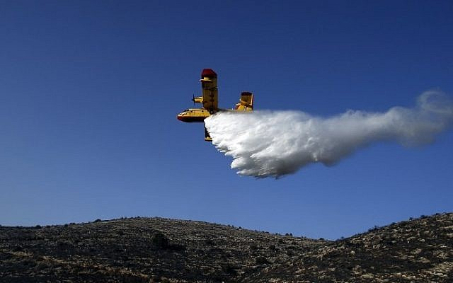 A foreign firefighting plane helps extinguish a fire as it flies over the village of Nataf close to Jerusalem, on November 26, 2016. (AFP Photo/Ahmad Gharabli)