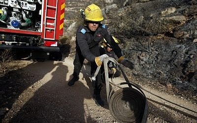 An Israeli firefighter unloads hose as they battle a fire in the village of Nataf close to Jerusalem, as it continues to spread in the area, on November 26, 2016. (AFP PHOTO / AHMAD GHARABLI)