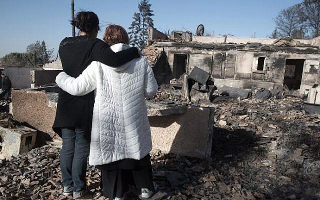 Israeli settlers grieve over their burnt houses in the Halamish settlement on November 27, 2016. AFP / MENAHEM KAHANA)