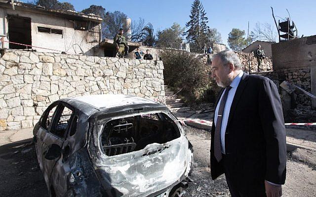 Avigdor Lieberman inspects burnt houses in the Halamish settlement on November 27, 2016. AFP/ MENAHEM KAHANA)