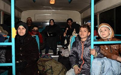 Syrian families, from various eastern districts of Aleppo, are evacuated by bus through Sheikh Maqsud, a Kurdish-controlled enclave between the government-held west of Aleppo and the east, on November 27, 2016 (AFP PHOTO / GEORGE OURFALIAN)
