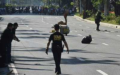 A member of police bomb disposal unit (R) holding a water bomb disruptor, walks towards the site where a suspicious package was found, for detonation along Roxas boulevard near the US embassy in Manila on November 28, 2016. (AFP PHOTO / TED ALJIBE)