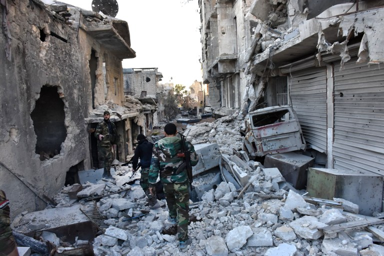 Syrian pro-government forces walk amidst heavy destruction in Aleppo's Bustan al-Basha neighborhood, November 28, 2016. (AFP/GEORGE OURFALIAN)