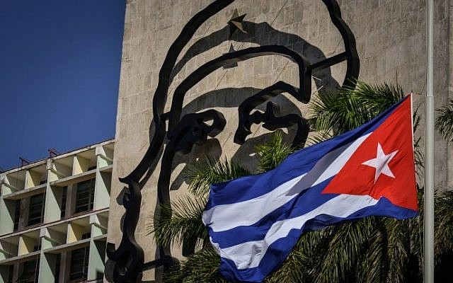 "The Interior Ministry building with the image of legendary guerrilla leader Ernesto ""Che"" Guevara and the Cuban flag fluttering at half mast at Havana's Revolution square, during revolutionary icon Fidel Castro memorial, on November 28, 2016 in Havana. (AFP PHOTO/ADALBERTO ROQUE)"