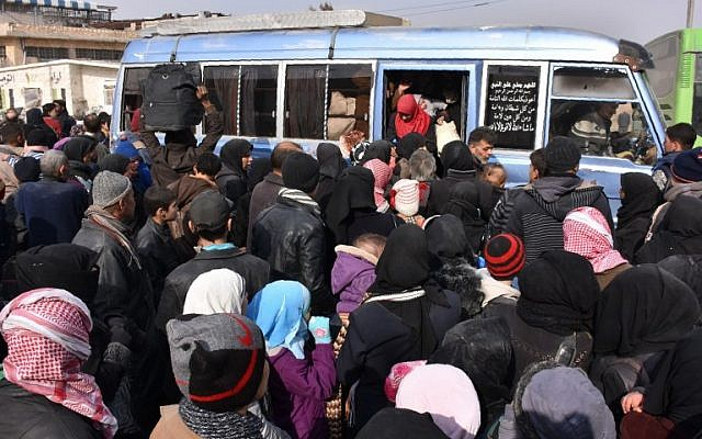 Syrian families, fleeing from various eastern districts of Aleppo, get onto a government bus on in the government-held eastern neighbourhood of Jabal Badro, November 29, 2016. (AFP/George OURFALIAN)