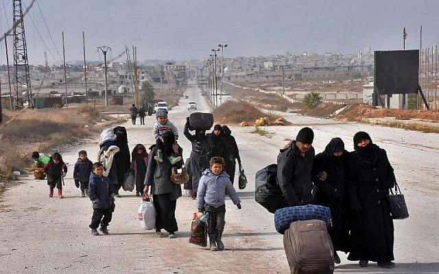 Syrian families, fleeing from various eastern districts of Aleppo, carry their belongings in the government-held eastern neighborhood of Jabal Badro, as they walk towards government-controlled western Aleppo, November 29, 2016. (AFP/George OURFALIAN)