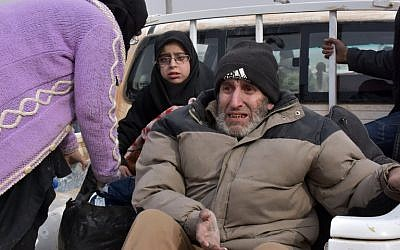 Syrian families, fleeing from various eastern districts of Aleppo, wait to board vehicles on November 29, 2016 in the government-held eastern neighborhood of Jabal Badro, before heading to government-controlled western Aleppo, as the Syrian government offensive to recapture rebel-held Aleppo has prompted an exodus of civilians. (AFP PHOTO / George OURFALIAN)