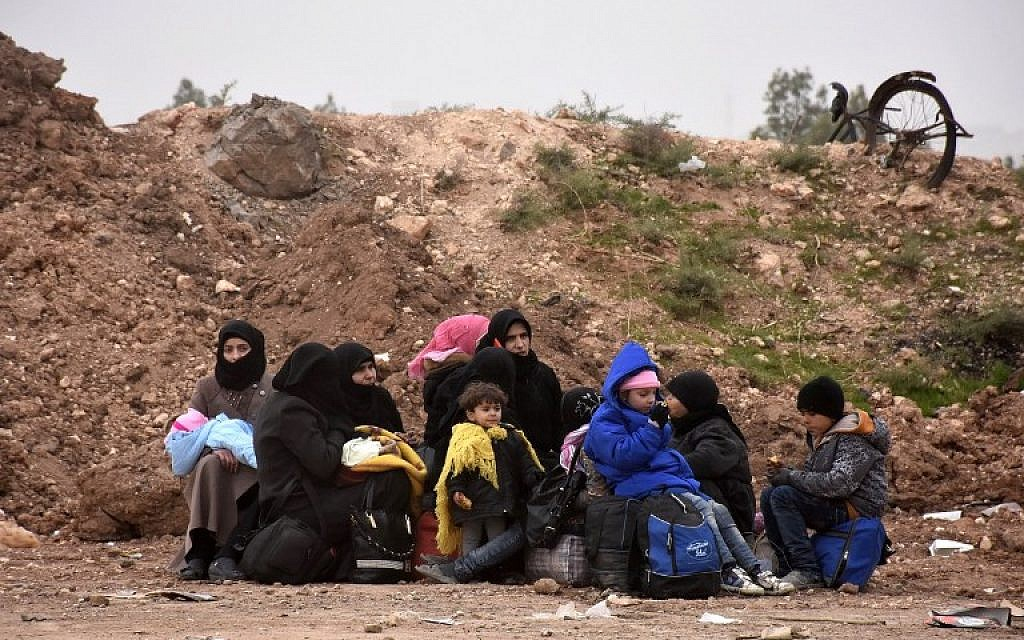 Syrian residents fleeing the eastern part of Aleppo sit on the side of the road after arriving at the Jabal Badro crossing point, which was recently retaken from rebel fighters by the regime forces, on November 30, 2016. (AFP PHOTO/George OURFALIAN)