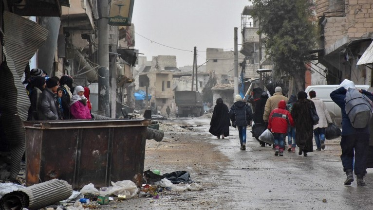 Syrian residents fleeing the eastern part of Aleppo walk through a street in Masaken Hanano, a former rebel-held district which was retaken by the regime forces last week, on November 30, 2016. (AFP Photo/George Ourfalian)