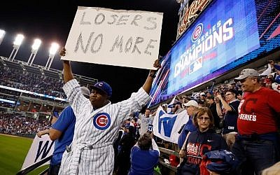 A Chicago Cubs fan holds a sign after the Cubs defeated the Cleveland Indians 8-7 in Game Seven of the 2016 World Series at Progressive Field on November 2, 2016 in Cleveland, Ohio. (Gregory Shamus/Getty Images/AFP)