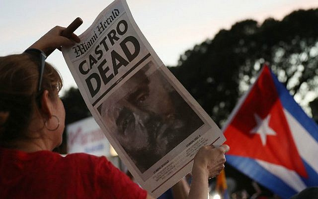 A person holds a poster printed by the Miami Herald with a headline that reads that the former Cuban President Fidel Castro is dead, outside the restaurant Versailles on November 26, 2016 in Miami, Florida. (Joe Raedle/Getty Images/AFP)