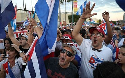 People dance together as they react to the news of the death of former Cuban President Fidel Castro outside the restaurant Versailles on November 26, 2016 in Miami, Florida. (Joe Raedle/Getty Images North America/AFP)