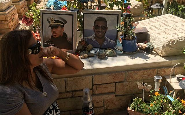 Irit Shahar at her son Omri's grave in Kfar Saba. (Courtesy)