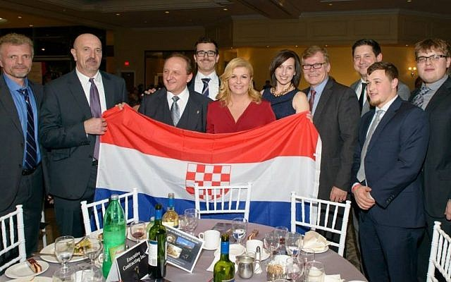 Croatian President Kolinda Grabar-Kitarovic poses during a recent trip to Canada with a flag carrying a symbol of her country's wartime pro-Nazi regime. (Facebook)